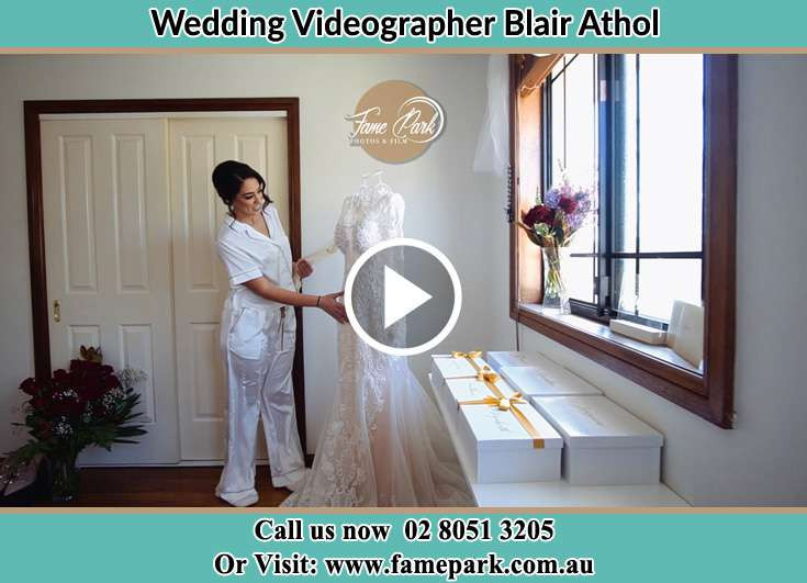 Bride looking at her wedding gown Blair Athol NSW 2560