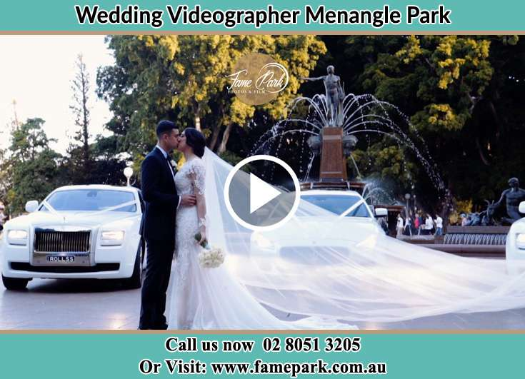 The new couple kissing near the wedding car Menangle Park NSW 2563